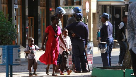 A woman and her children walk past Zimbabwean police in Harare