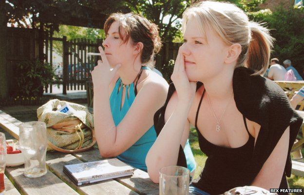 Two women are sat in a beer garden, one is smoking a cigarette
