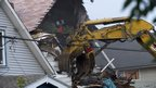 A digger destroys the house of Ariel Castro, where he kept three women captive for over a decade
