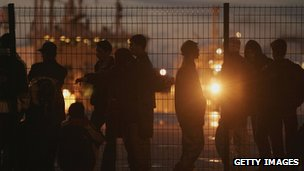 A group of people in shadow at a fence in Calais