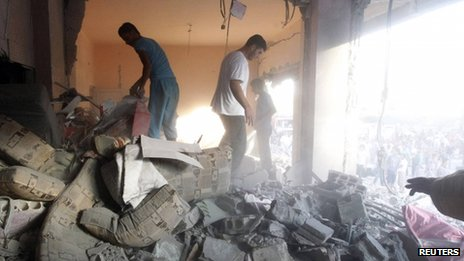 Men search for survivors amid debris of collapsed buildings, after what activists said was shelling by forces loyal to Syrian President Bashar al-Assad in Raqqa province, eastern Syria, 7 August
