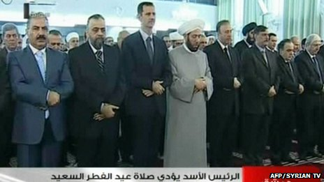 An image grab taken from the state-run Syrian television on 8 August, 2013, shows Syrian President Bashar al-Assad (3rdL) and Syrian Grand Mufti Ahmed Hassun (C) attending the morning prayer of Eid al-Fitr in Damascus.