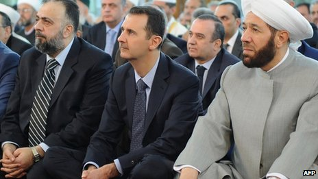 A handout picture released by the Syrian Arab News Agency (SANA) on 8 August, 2013 shows Syrian President Bashar al-Assad (C) and Syrian Grand Mufti Ahmed Hassun (R) attending the Eid al-Fitr morning prayer in Damascus.
