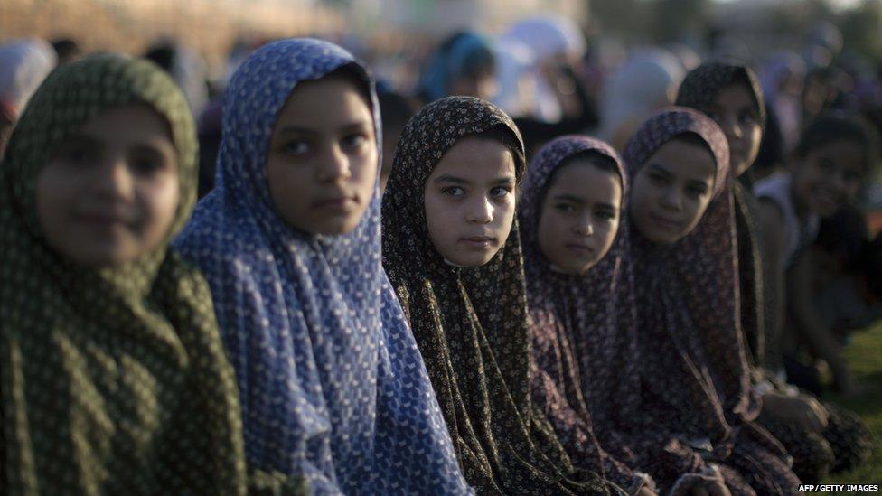 Palestinian girls take part in the morning Eid al-Fitr prayer in Gaza City (8 August 2013)