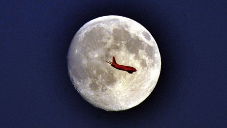 A plane crosses in front of a full moon. The plane is red from the setting sun