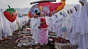 "A girl eats ice cream as Indonesian Muslims perform Eid Al-Fitr prayer on ""sea of sands"" at Parangkusumo beach on August 8, 2013 in Yogyakarta, Indonesia"