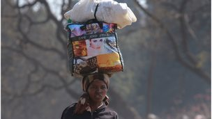 A woman carries her luggage in central Harare, Thursday 8 August, 2013.