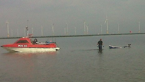 Sunken boat being towed back to shore