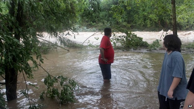 Nick Ramirez looks downstream for signs of his trailer, which was swept away by flood waters in Hollister, Missouri, on 8 August 2013