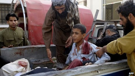 Pakistani bystanders help an injured Muslim youth as he sits in a pickup truck amidst bodies outside a hospital in Quetta on 9 August, 2013, following an attack by gunmen on a mosque.