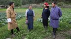 Bhutanese men in traditional robes visiting farm workers Tashi Dema and Tshering Pelden.