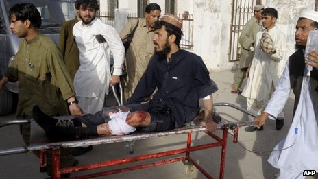 Pakistani bystanders help an injured Muslim man as he sits on a stretcher outside a hospital in Quetta on 9 August, 2013, following an attack by gunmen on a mosque.