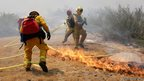 Firefighters rush to move their hose from spreading flames as the Silver Fire burns in the foothills in Cabazon, California