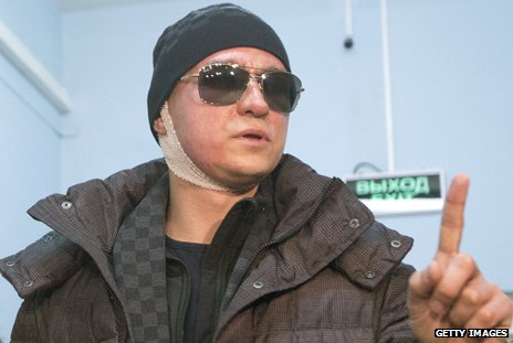 Sergei Filin is shown with a bandage around his neck, wearing a hat and dark glasses