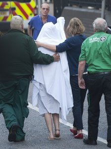 One of the victims, with head and face covered, arrives at Chelsea and Westminster Hospital,