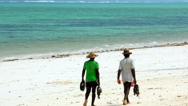 People walk along a beach in Zanzibar carrying fish