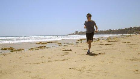 Kevin Fong running along a beach