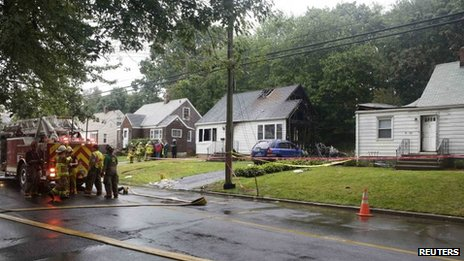 A fire truck and burnt homes are pictured at the site of a plane crash in East Haven