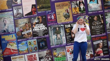 Girl in front of Edinburgh Fringe posters