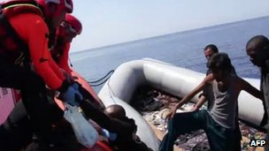 A picture released by the Italian coast guards shows coast guards puling a man as they help immigrants out of their dinghy on August 8, 2013 in the Mediterranean, off Lampedusa