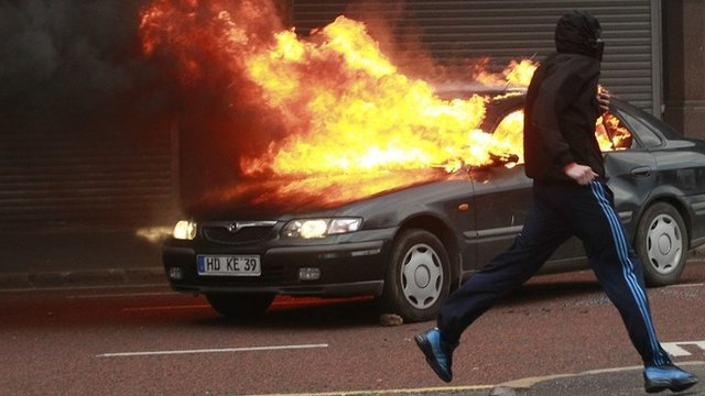 A protestor runs past a burning car during rioting in the centre of Belfast