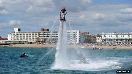 A man entertains crowds with a water jet pack at Worthing Birdman