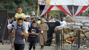 Supporters of Egypt's ousted President Mohammed Morsi walk through makeshift barriers to a sit-in at Nahda Square