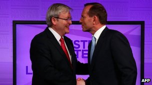 Australian Prime Minister Kevin Rudd talks with conservative opposition leader Tony Abbott before the debate on 11 August 2013