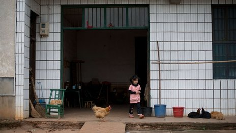 )n April 30, 2012 a child of migrant workers leaves the home she shares with her grandmother in the village of Zhuangshuzui, Hunan province