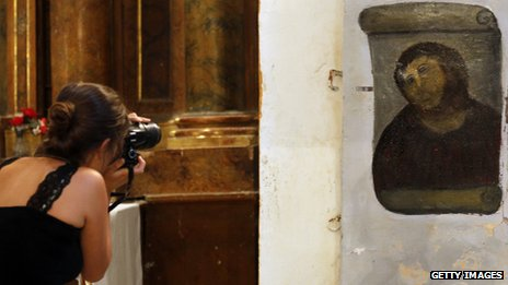 A tourist takes a photograph of Ecce Homo