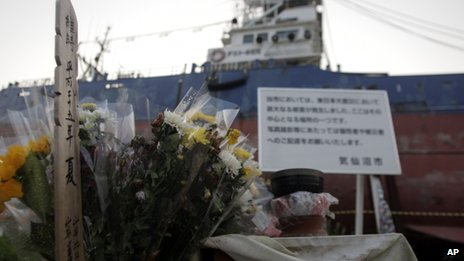 In this photo taken on 11 August 2013, flowers and gifts are left by a stranded fishing boat standing in a residential district of Kesennuma, Miyagi prefecture, northern Japan