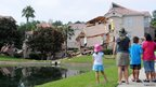 People look at a partially collapsed building over a sinkhole at Summer Bay Resort near Disney World on August 12, 2013 in Clermont, Florida. The 40 to 60 foot sinkhole opened up under the resort building reportedly begining late August 11 into early August 12. There were no injuries or deaths reported.