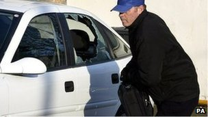 A thief breaks into a car during a mock-up by the Police Service of Northern Ireland in Belfast, Monday November 21, 2005.
