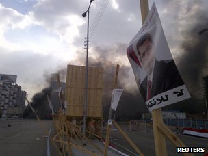 A poster of deposed Islamist President Mohammed Morsi in front of smoke rising from Rabaa al-Adawiya camp on 14 August