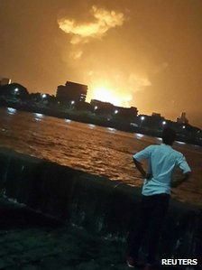 A man watches Indian Navy submarine INS Sindhurakshak on fire in Mumbai August 13, 2013