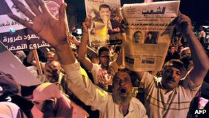 Muslim Brotherhood supporters shout slogans as they wave portraits of Egypt's ousted president Mohamed Morsi