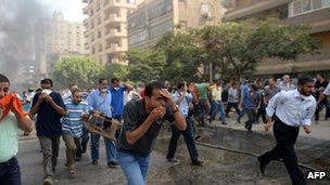 Egyptian Muslim Brotherhood supporters flee tear gas fired by police in a street leading to Rabaa al-Adawiya camp in Cairo on 14 August 2013