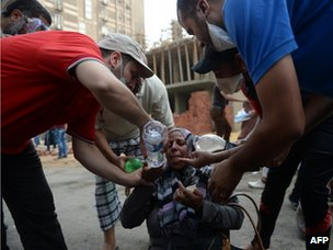 Muslim Brotherhood supporters help a woman suffering from tear gas exposure near the Rabaa al-Adawiya camp on 14 August 2013