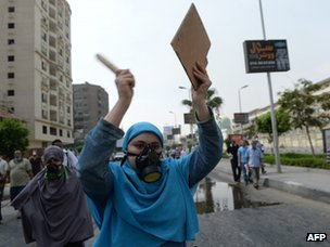 Muslim Brotherhood supporters wear gas masks to protect against exposure to tear gas on 14 August 2013
