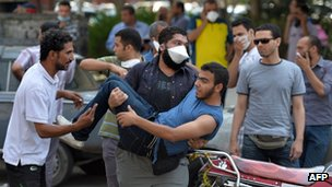 A protester carries an injured Morsi supporter after clashes with police near a protest camp on 14 August 2013