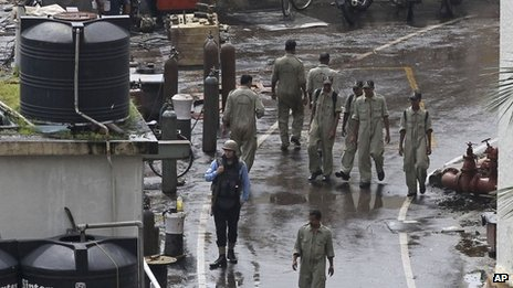 Indian navy sailors walk at the naval dockyard where a submarine caught fire and sank after an explosion early Wednesday in Mumbai, India, Wednesday, Aug. 14, 2013