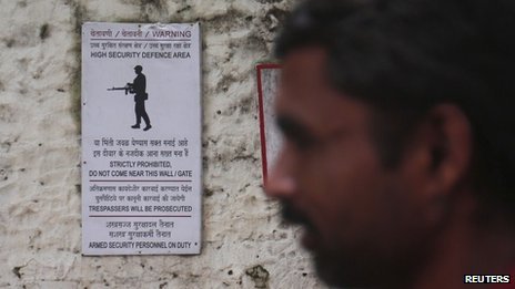 A man walks past a warning sign at a gate at the naval dockyard in Mumbai August 14, 2013