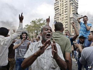 Supporters of ousted President Mohammed Morsi chant slogans against Egyptian Defence Minister Gen Abdel Fattah Sissi during clashes with Egyptian security forces in Cairo's Mohandessin neighbourhood on 14 August