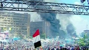 Smoke rising behind protesters in Cairo - 14/8/2013