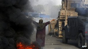 An Egyptian woman tries to stop a military bulldozer from going forward during clashes at a protest camp near Rabaa al-Adawiya mosque on 14 August 2013