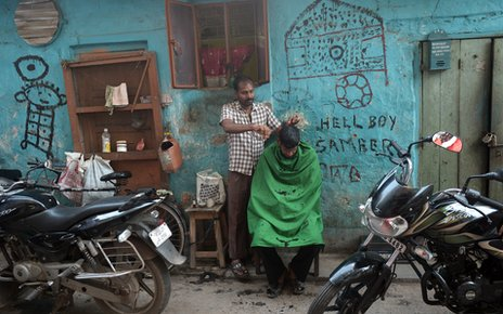 A man cuts hair near the residential complex where Badar Azim lives