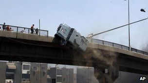 Police vehicle pushed off 6th October Bridge by protesters in the eastern Nasr City district of Cairo, 14 August 2013