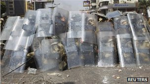 Riot police and army soldiers protect themselves with riot shields as Muslim Brotherhood supporters throw stones during clashes around the area of Rabaa al-Adawiya square on 14 August 2012