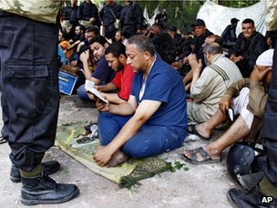 Riot police stand guard over detained supporters of deposed Egyptian president Mohammed Morsi, as they read from the Koran, in the smaller protest camp close to Cairo University on 14 August 2013