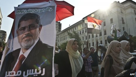 An Egyptian supporter of Mohammed Morsi holds a poster of him